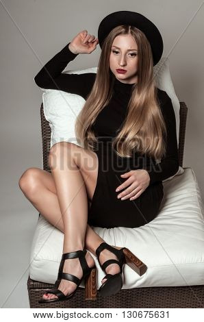 Beauty woman with long wavy blond hair in a black hat and black dress on a sofa. Beautiful model with fresh make up and red lips.