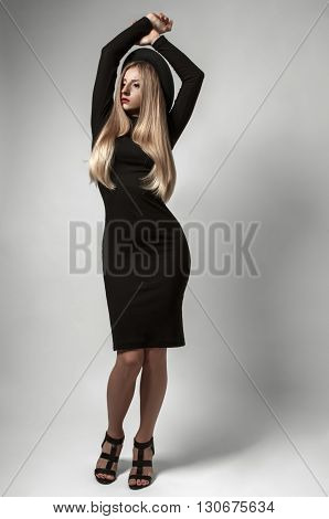Beautiful woman with long straight blond hair in a black hat in the studio. Blonde model with evening make up wearing a black dress and high-heeled shoes.