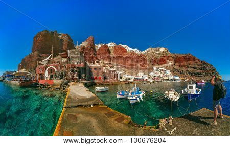 Photographer traveler takes pictures of Old port Amoudi of Oia village at Santorini island in Aegean sea, Greece