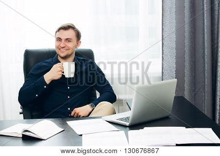 Smiling relaxed male designer in casual clothes work drinking coffee at his desk.