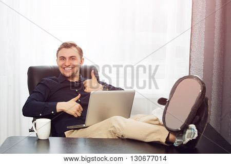 Legs on the desk, laptop and smiling man with thumbs up gesture