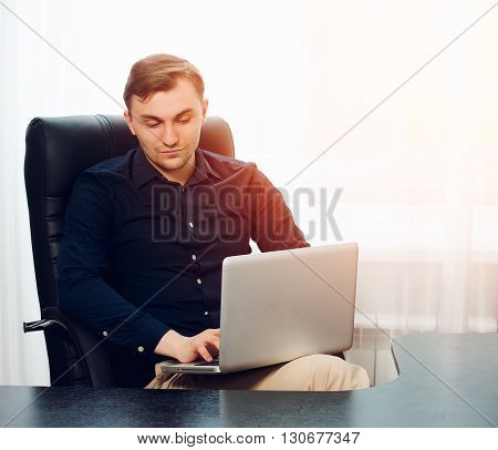Square picture of leisurely working businessman in chair