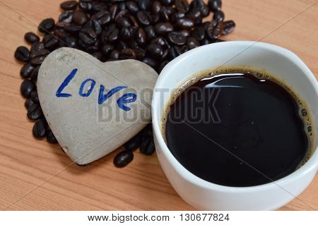 black coffee cup and bean with heart rock