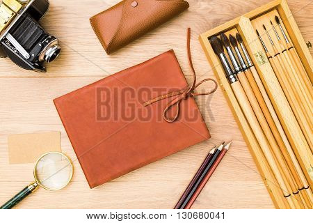 Top view of wooden desktop with closed leather notepad retro camera magnifier set or brushes and other items