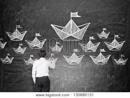 Leadership concept with businessman drawing paper boats on chalkboard