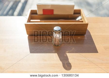 Glass salt shaker on a wooden table in a restaurant placed next to a wooden box of folks and napkins backlit by morning sunlight casting long shadow selective focus on the shaker's lid with shallow depth of field
