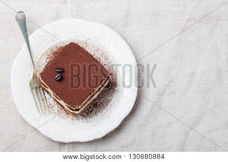 Tiramisu, traditional Italian dessert on a white plate Top view Copy space
