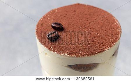 Tiramisu, traditional Italian dessert in glass on a grey stone background