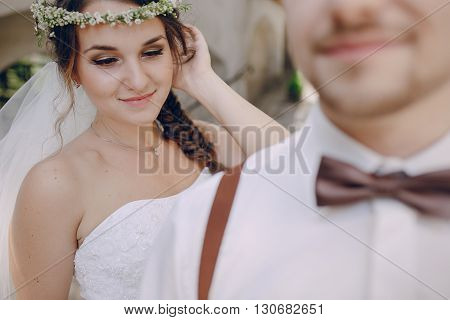 charming wedding couple in wreaths and suspenders