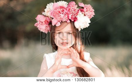 Beautiful kid girl 4-5 year old making heart with hands outdoors. Looking at camera. Childhood.