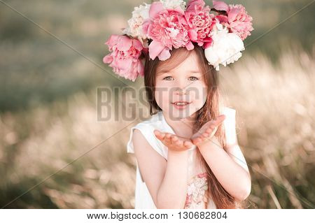 Smiling baby girl 4-5 year old posing outdoors, wearing peony wreath. Looking at camera. Childhood.