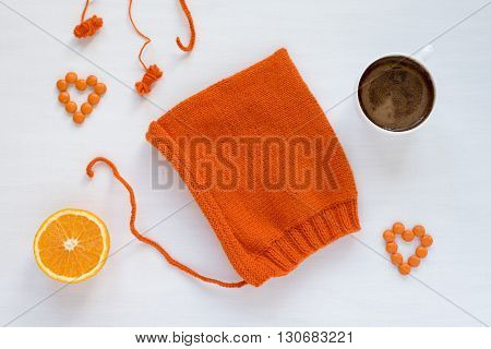 Cup of coffee, orange, candies and a handmade hat on white background