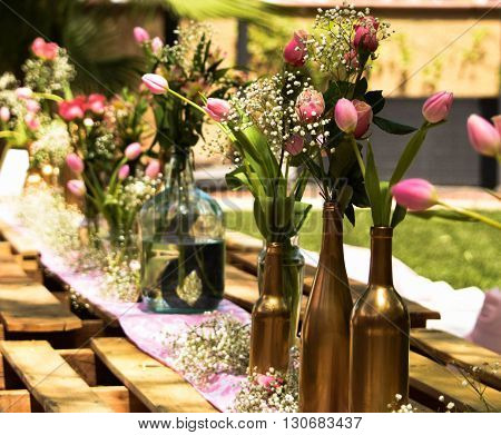 Outdoor garden party decorated on wooden pallets with pink tulips in gold bottles for a bridal shower