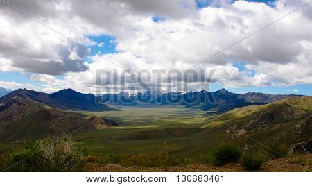 Alpine meadow and surrounding mountains with afternoon cloud buildup