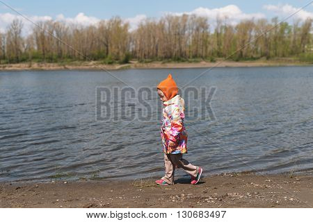 little girl walking along the riverbank on a sunny day.
