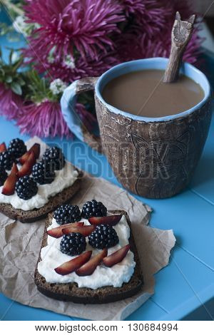 Sandwiches With Sweet Cheese And Berries, A Cup Of Coffee And A Bouquet Of Asters In Blue Wooden Bac