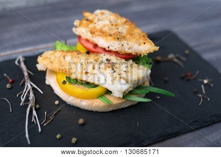 Fish grilled with tomato pepper green onion on the bread on the stone blackboard
