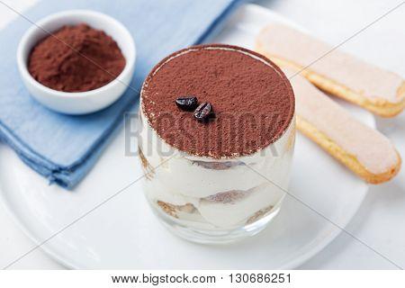 Tiramisu, traditional Italian dessert in glass on a grey stone background.