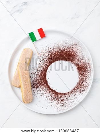 Ingredients for tiramisu dessert with Italian flag on a white plate, savoiardi cookies, cocoa powder. Copy space. Marble background