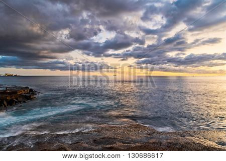 Rocks at topical beach at beautiful sunset.Costa Adeje, Tenerife, Spain
