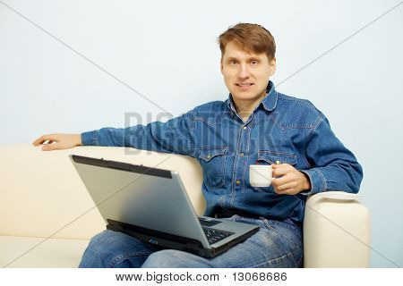 Person Reads News In Internet At Home On Sofa