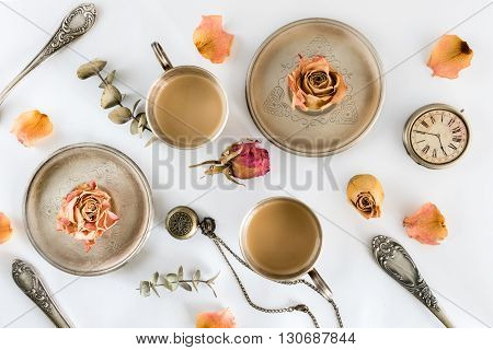 Two cups of coffee with roses and watch. Flat lay. Top view