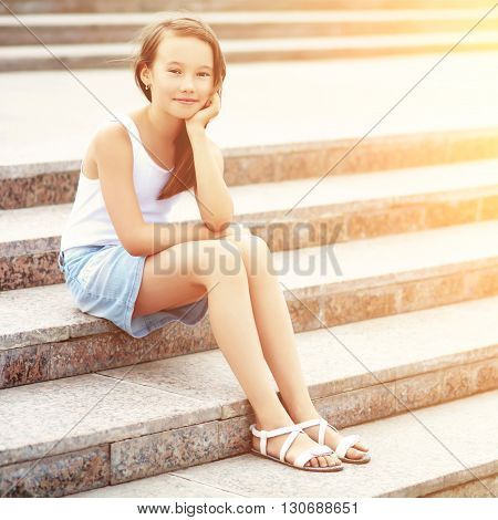portrait of a cute girl sitting on the stairs