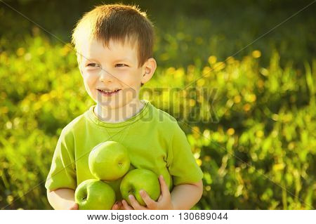 Cheerful smiling boy with green apples. child with fruit on a green background