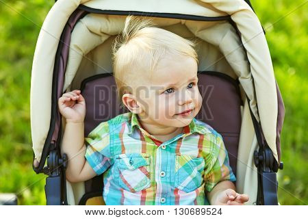 little boy sitting in a stroller. baby for a walk in a pram. summer outdoors