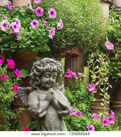 charm angel sculpture with flower in the garden