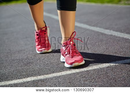 selective focus. runner feet closeup. athlete running on jogging track at the stadium in running shoes. jogging outdoors
