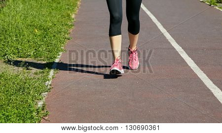 selective focus.. runner feet closeup. athlete running on jogging track at the stadium. running shoes. jogging outdoors