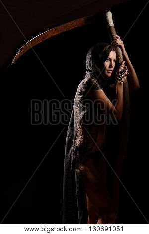Girl in a black lace smock with a scythe of death. concept