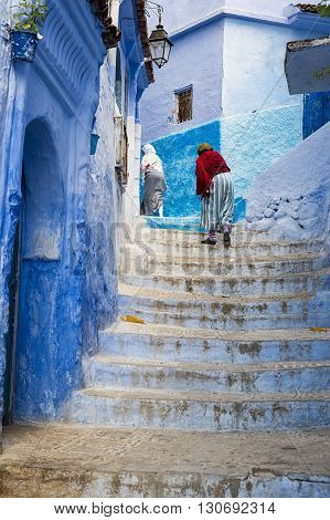 Chefchaouen Morocco - April 10 2016: Women climbing a stair in the town of Chefchaouen in Morocco.