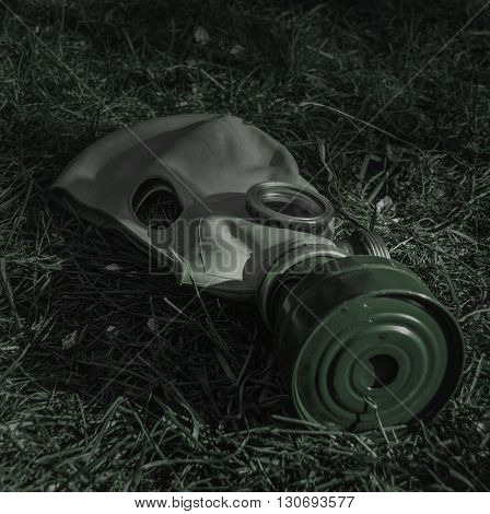 The old Soviet gas mask on the grass in the gloom of night