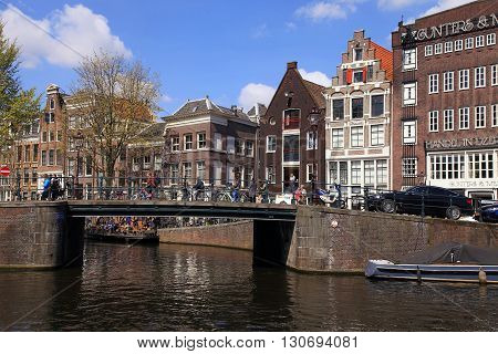 AMSTERDAM, NETHERLANDS - MAY 4, 2016: City scene with bridge and old houses of traditional architecture along a canal in Amsterdam, Netherlands. Amsterdam is the capital and most populous city of the Netherlands.