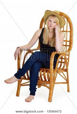 Dreamy Girl Is Sitting In A Wicker Chair