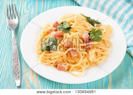 Pasta Carbonara with ham and cheese on blue wooden suface. Top view.