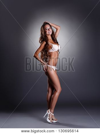 Smiling woman posing in sexy lingerie and high heels