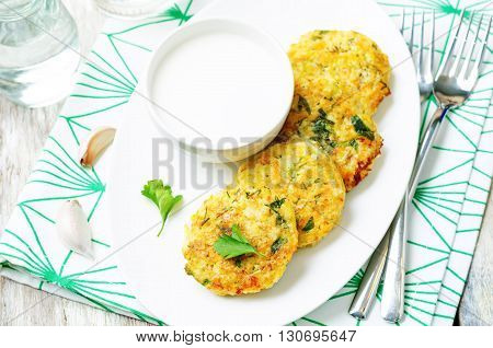 Cheesy millet zucchini fritters on a white wooden background.