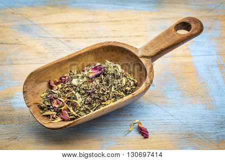 Rustic wooden scoop of healthy stomach herbal tea -  a blend of  peppermint, spearmint, ginger, hibiscus, rosehip, red rose,almond, and osmanthus.