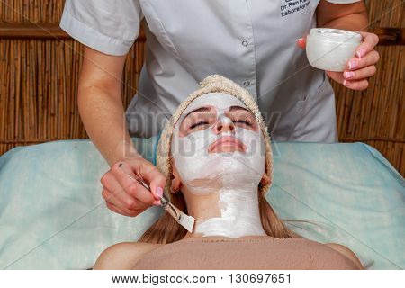 Applying the mask to the face of a young girl. Facial skin at spa salon