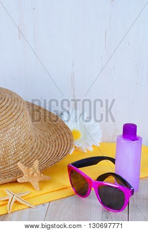 Summer still life with straw hat, bright purple sunglasses, a yellow towel, a pretty daisy, a purple bottle of lotion and some starfish, all on a wooden surface and white-washed wooden background