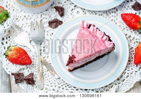 Strawberry mousse brownie cake on white wood background.