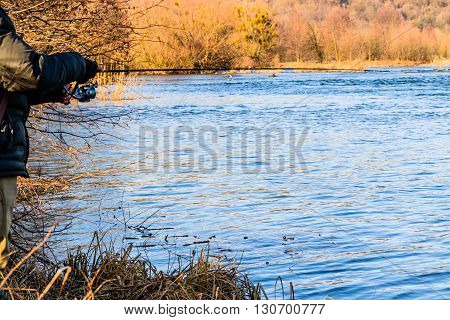Fisherman on the river bank. Sport fishing.