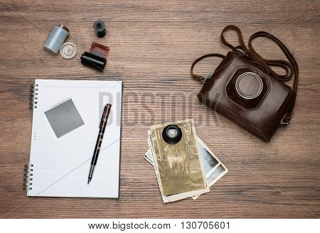 Photo accessories in vintage style. Retro still camera in its case films cassette loupe some old photos notebook and ink pen on table.