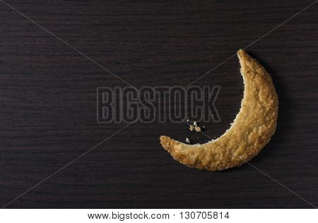 Bite of a cookie biscuit in moon shape. Moon-shaped cookie - creative idea.