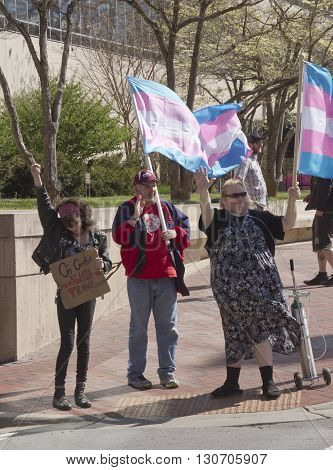 Asheville, North Carolina, USA - April 2, 2016: People stand on a street corner holding flags and signs protesting the new North Carolina HB2 Law that restricts the rights of those who are gay or transgender