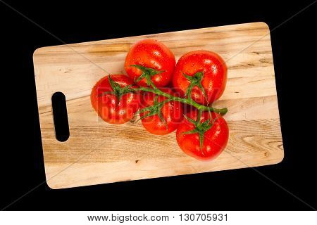 Red tomatoes on a black background isolated. Selective focus.