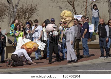 Asheville, North Carolina, USA - February 28, 2016: A Donald Trump Effigy kneels before Hillary Clinton and Mr. Monopoly characters holding money bags as a crowd of Bernie Sanders supporters with signs watch at a Bernie Sanders campaign rally